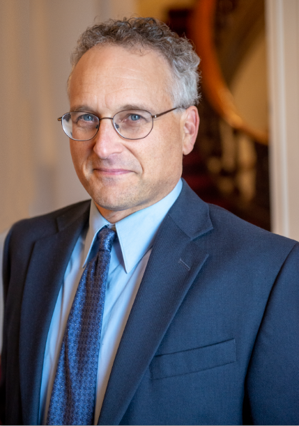 A professional man wearing a suit and glasses.
