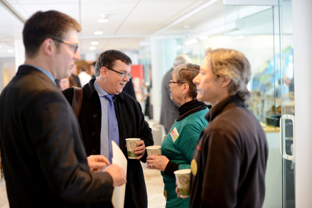 Four professional men and women holding coffees talking to each other at the Vermont State House.
