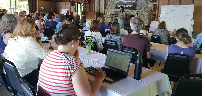 A group of people sitting at tables in a rustic space watching a woman make a presentation.