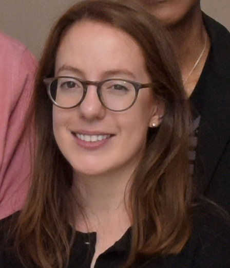 A young professional woman, smiling and wearing glasses.