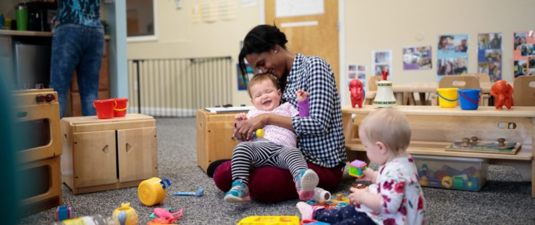 An early childhood educator interacting with two young children in a classroom.
