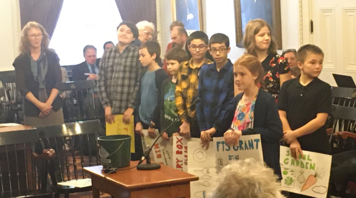 Students at the Vermont State House holding homemade signs supporting Farm to School.