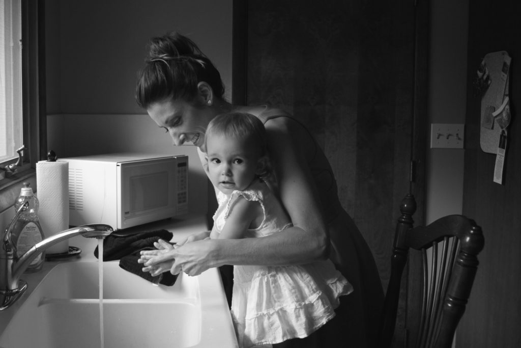 A woman and small child washing their hands at a sink.
