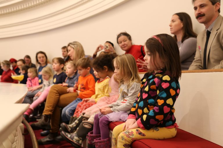 Young children in bright colors seated in the gallery at the Vermont State House.