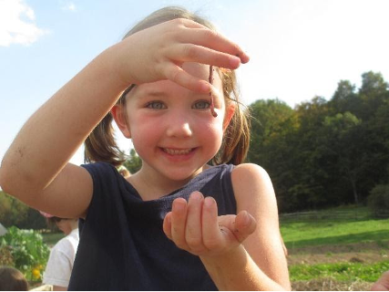 Smiling young girl holds up a worm.